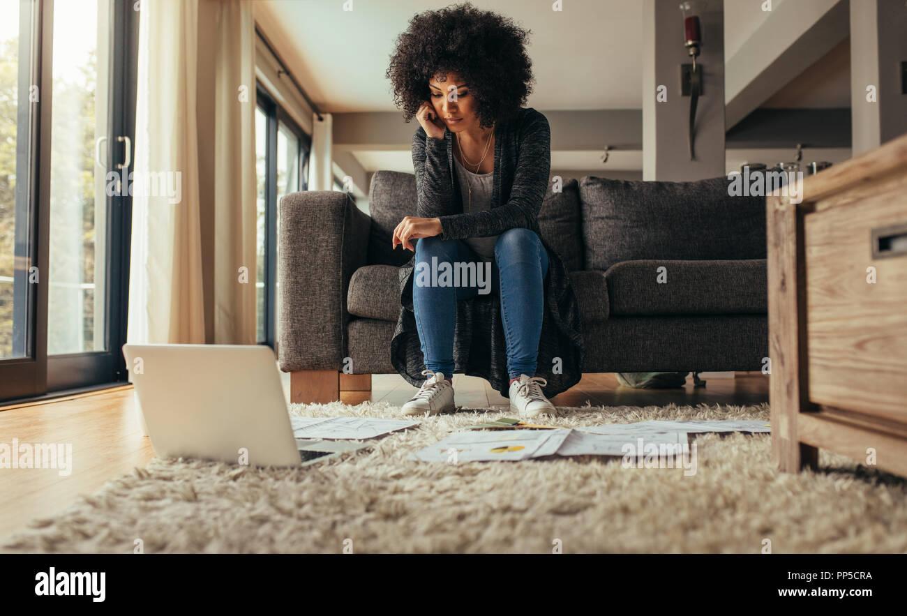Donna seduta in divano con pochi documenti sul pavimento con un computer portatile. Donna al lavoro su un nuovo piano di business da casa. La donna lo studio b Foto Stock