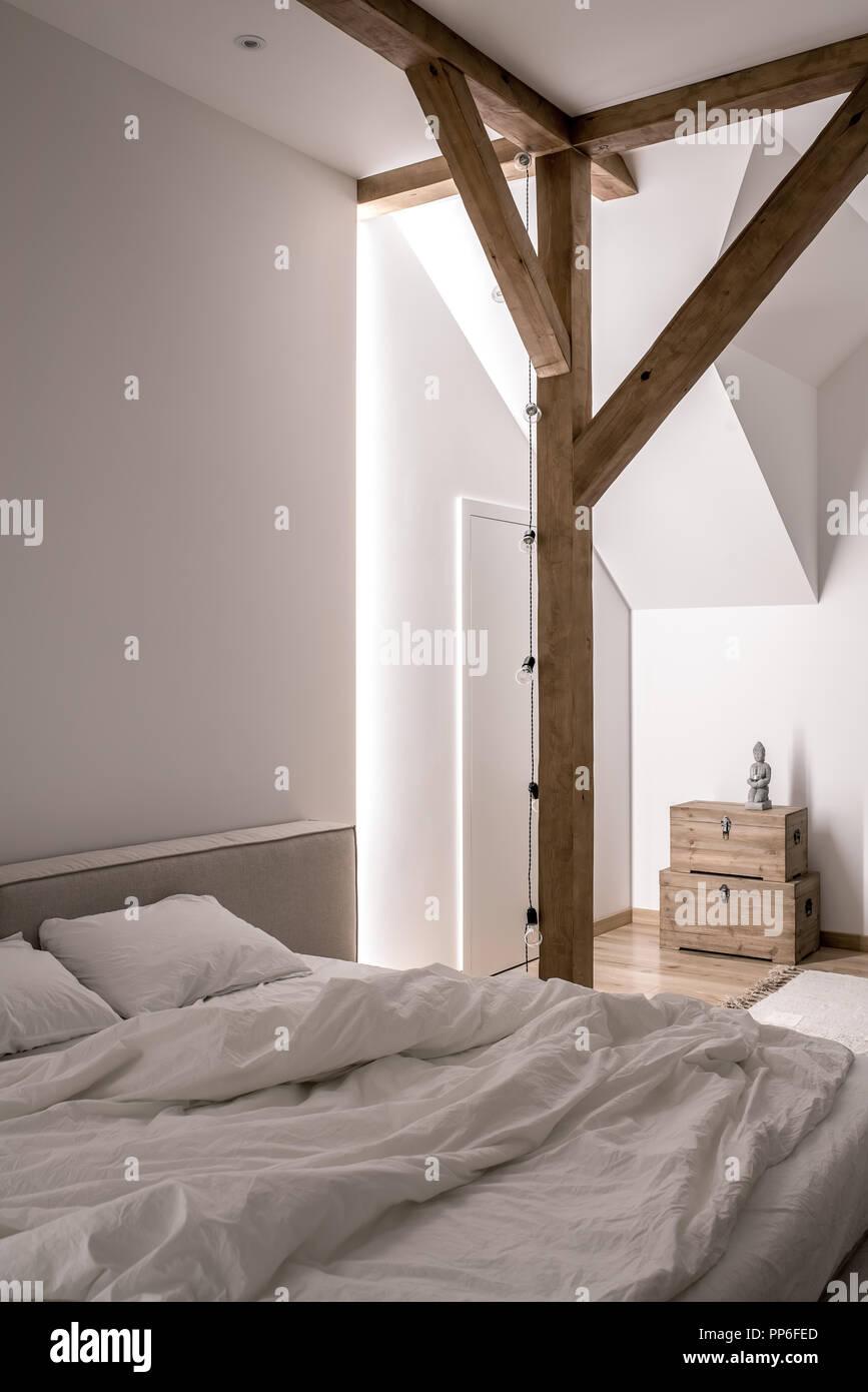 Illuminato camere da letto moderne con pareti bianche, travi in ...