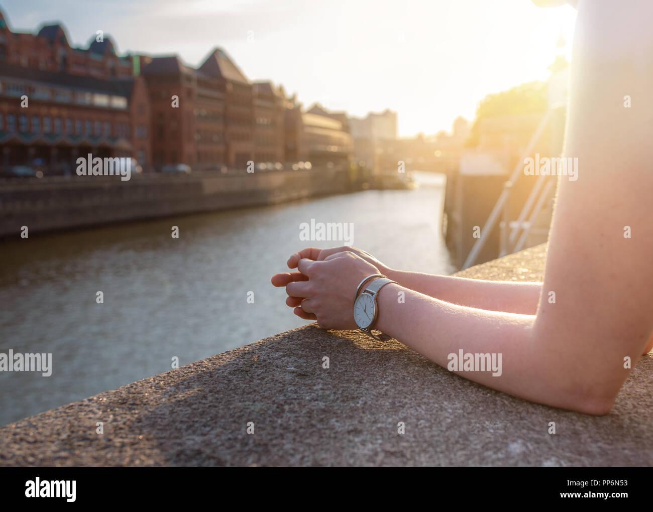 Vista parziale di donna in appoggio le sue braccia sulla parete quay Foto Stock