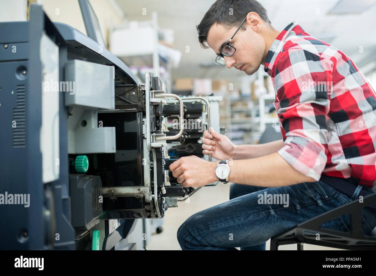 Uomo informale lavora con macchina da stampa Immagini Stock