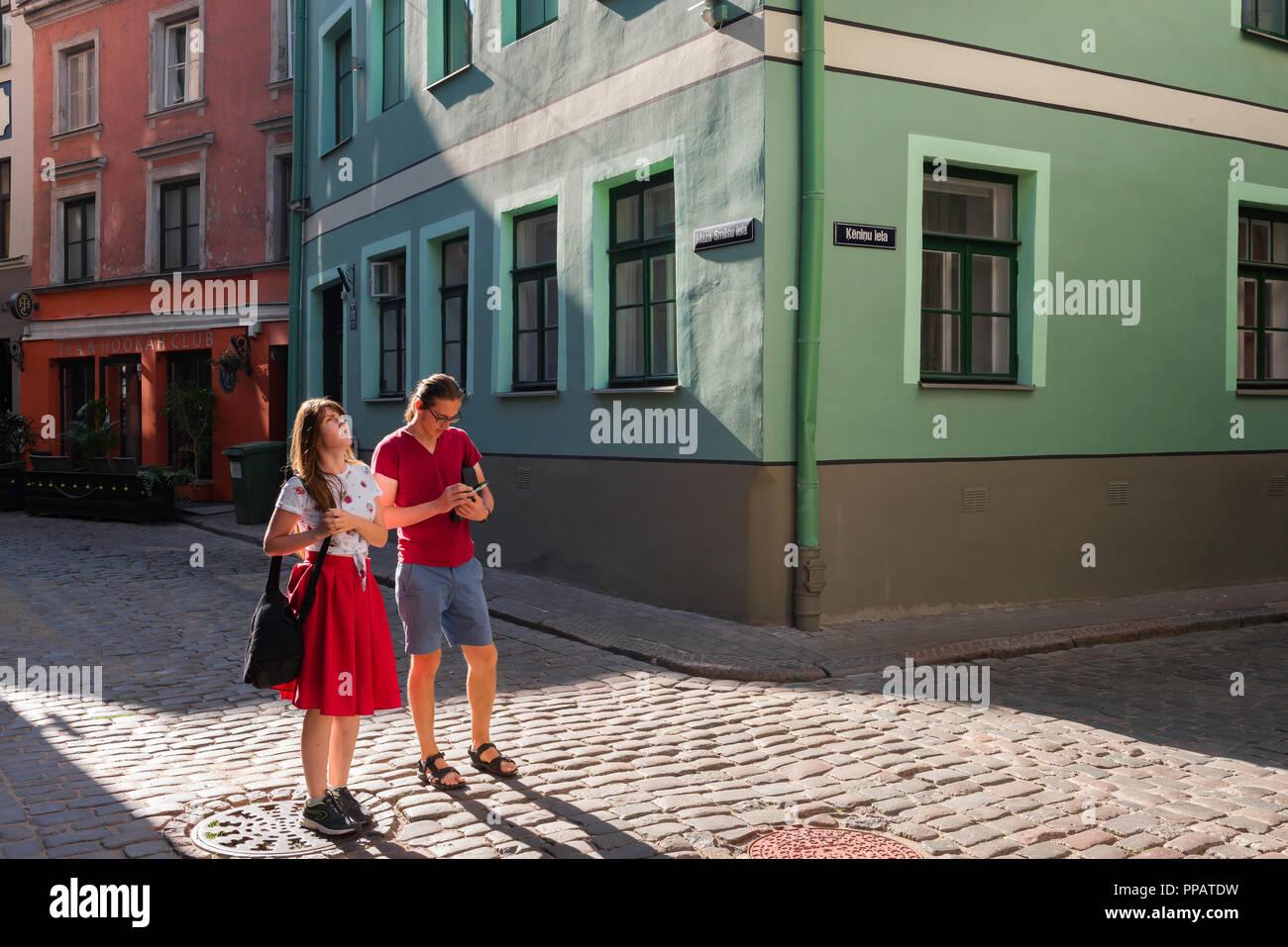 Riga Old Town street, su una mattina d'estate due giovani turisti sightseeing (18-25) navigare le strade medievali di Riga Old Town, Lettonia. Foto Stock