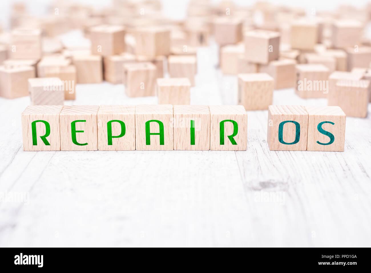 Le parole riparare OS formata da blocchi di legno su un tavolo bianco Immagini Stock