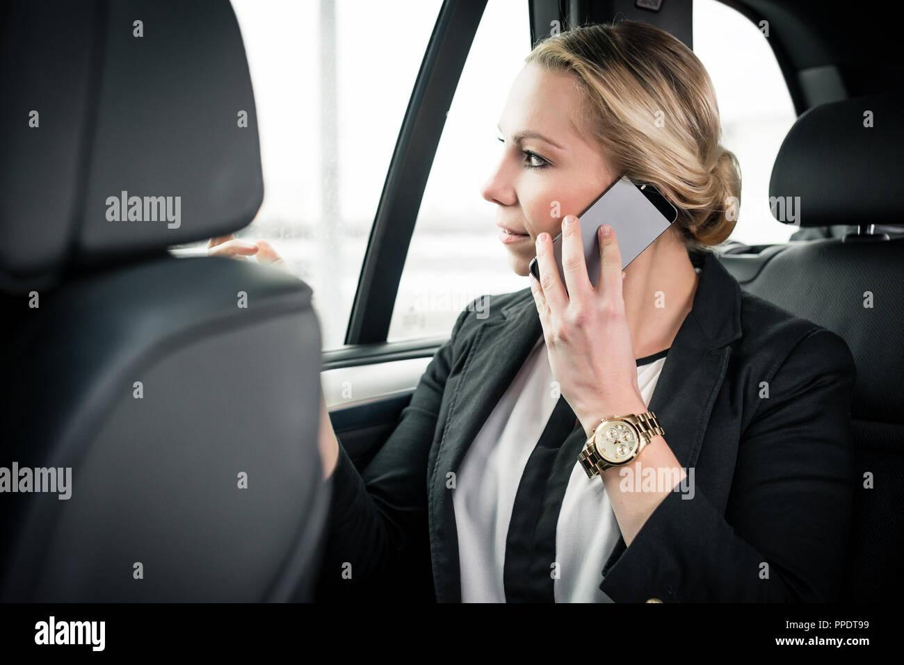 Imprenditrice seduti in auto parlando al cellulare Immagini Stock