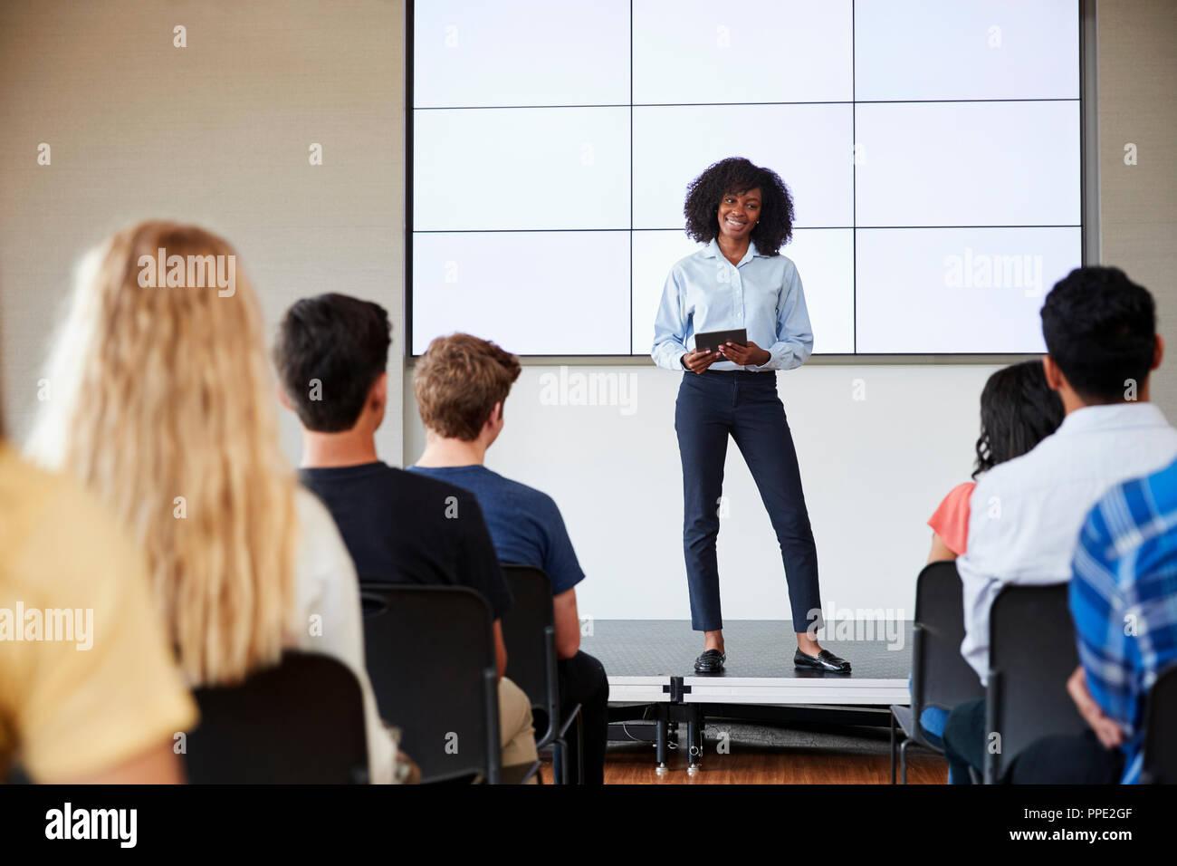 Insegnante femmina con tavoletta digitale dando la presentazione alla scuola di alta classe nella parte anteriore dello schermo Foto Stock