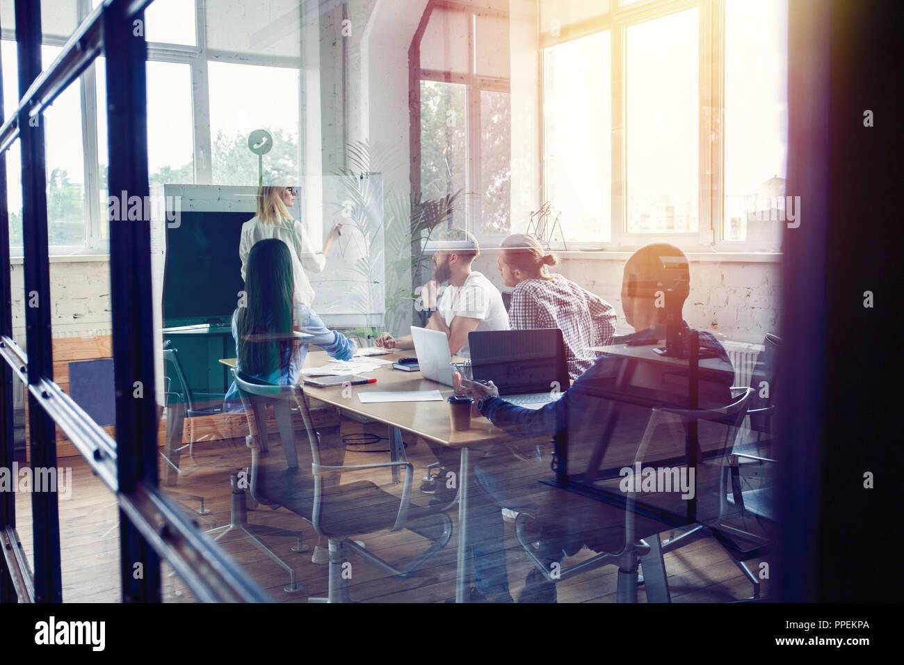 Lavorando duro per vincere. Imprenditrice condurre una presentazione con lavagna a fogli mobili mentre si lavora in ufficio creativo. Immagini Stock