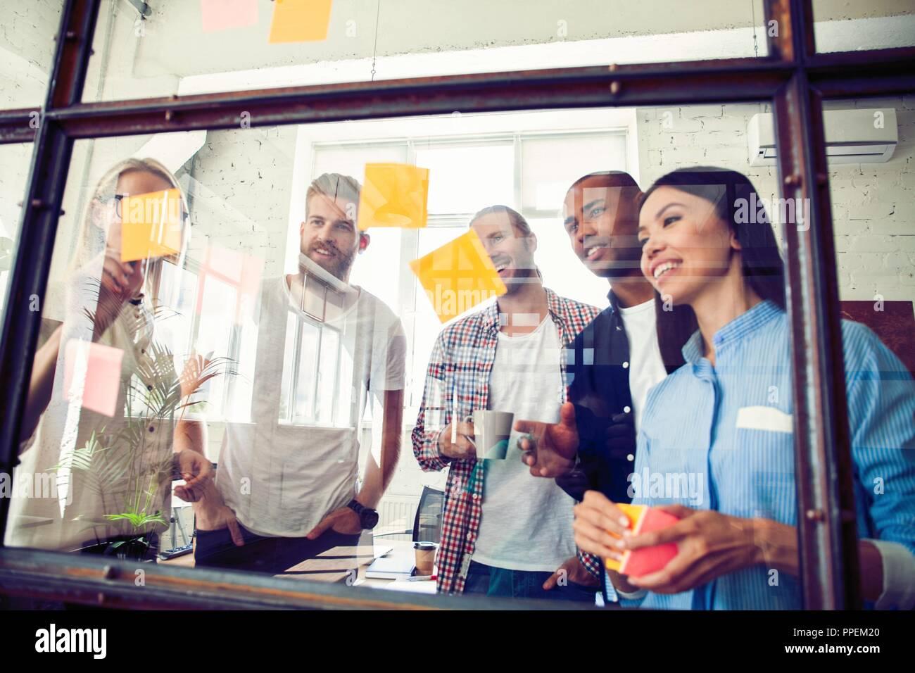 La gente di affari riunione in ufficio e uso di post-it per condividere idea. Concetto di brainstorming. Nota adesiva sulla parete di vetro Immagini Stock