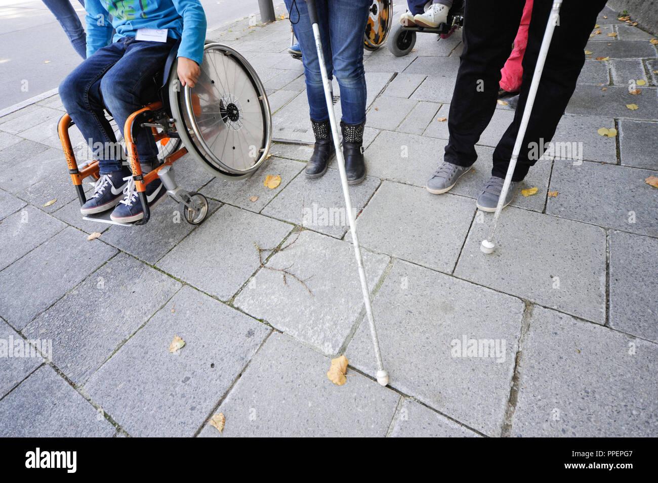 Bambini possono provare come si sposta con disablities attraverso la città insieme con i caregivers di KJR e persone disabili. Il loro parere va quindi a organi politici quali il Comitato Distrettuale, Monaco di Baviera, Germania Immagini Stock