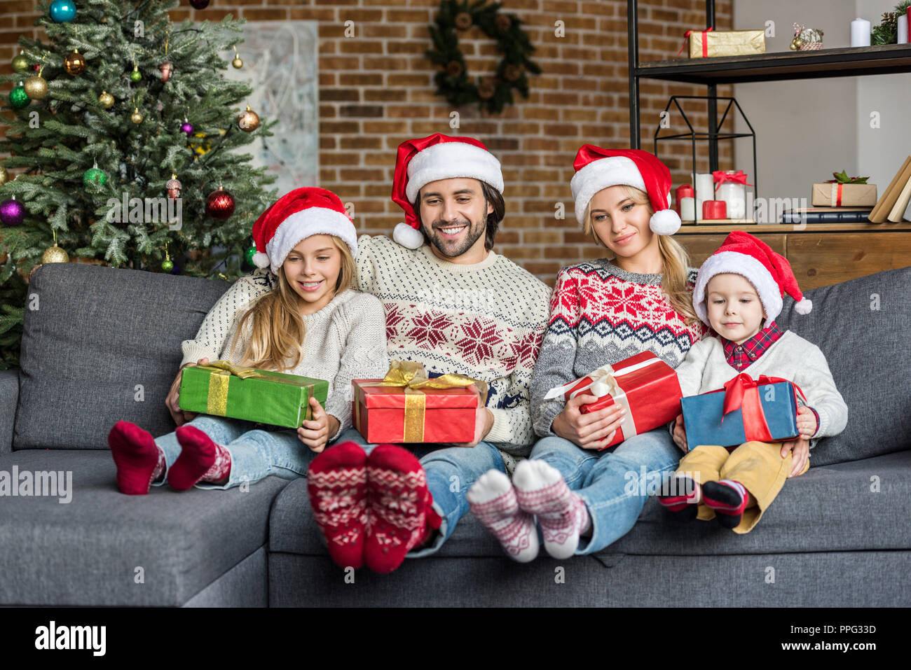 Regali Di Babbo Natale.La Famiglia Felice In Cappelli Di Babbo Natale Tenendo I Regali Di Natale E Seduti Insieme A Casa Foto Stock Alamy