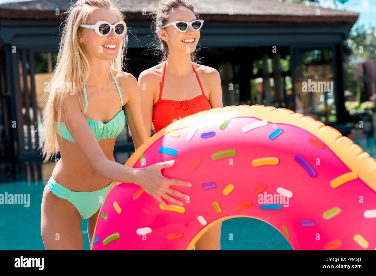 Felice di giovani donne con anello gonfiabile a forma di ciambella in piedi sul bordo della piscina e guardando lontano Immagini Stock