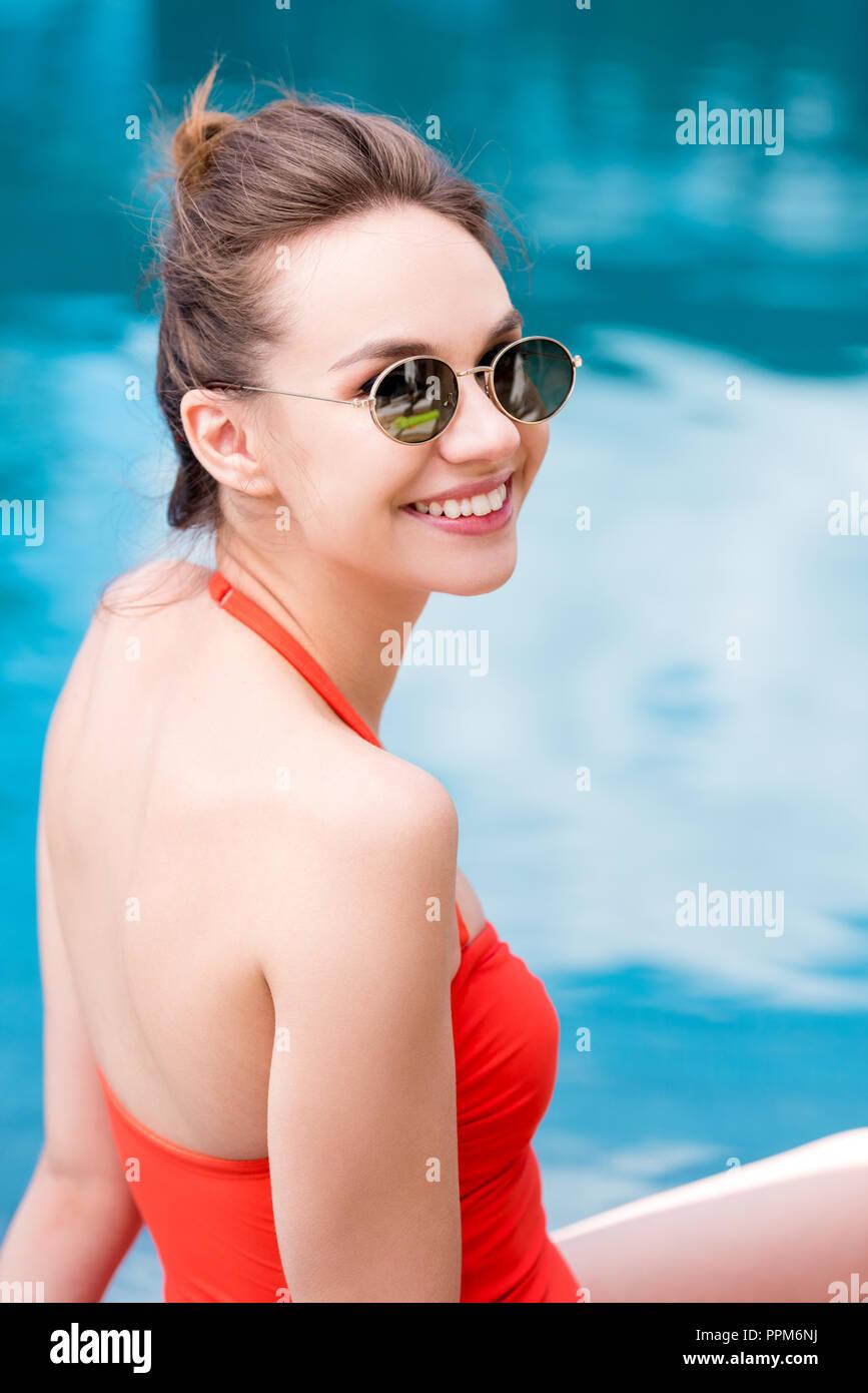 Felice giovane donna in costume da bagno rosso a bordo piscina Immagini Stock