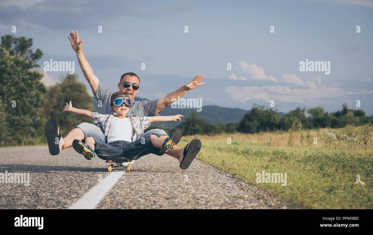 Padre e figlio giocando sulla strada al giorno. Le persone aventi il divertimento all'aperto. Concetto di famiglia amichevole. Immagini Stock