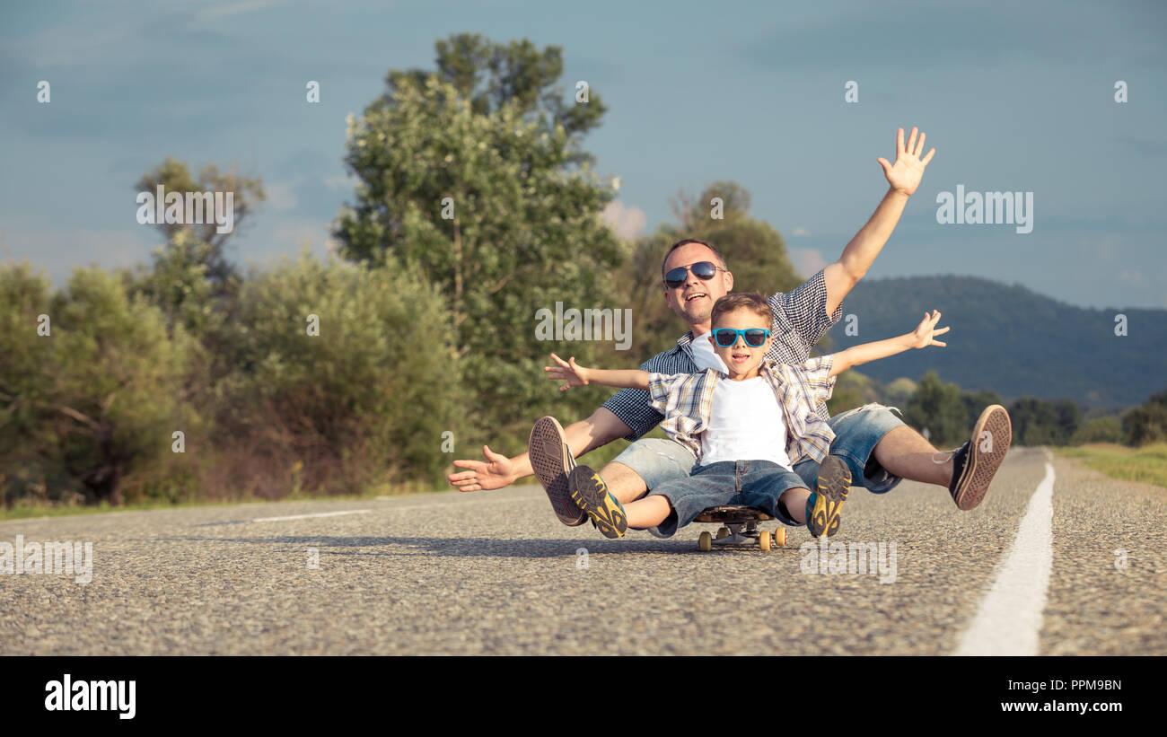 Padre e figlio giocando sulla strada al giorno. Le persone aventi il divertimento all'aperto. Concetto di famiglia amichevole. Foto Stock
