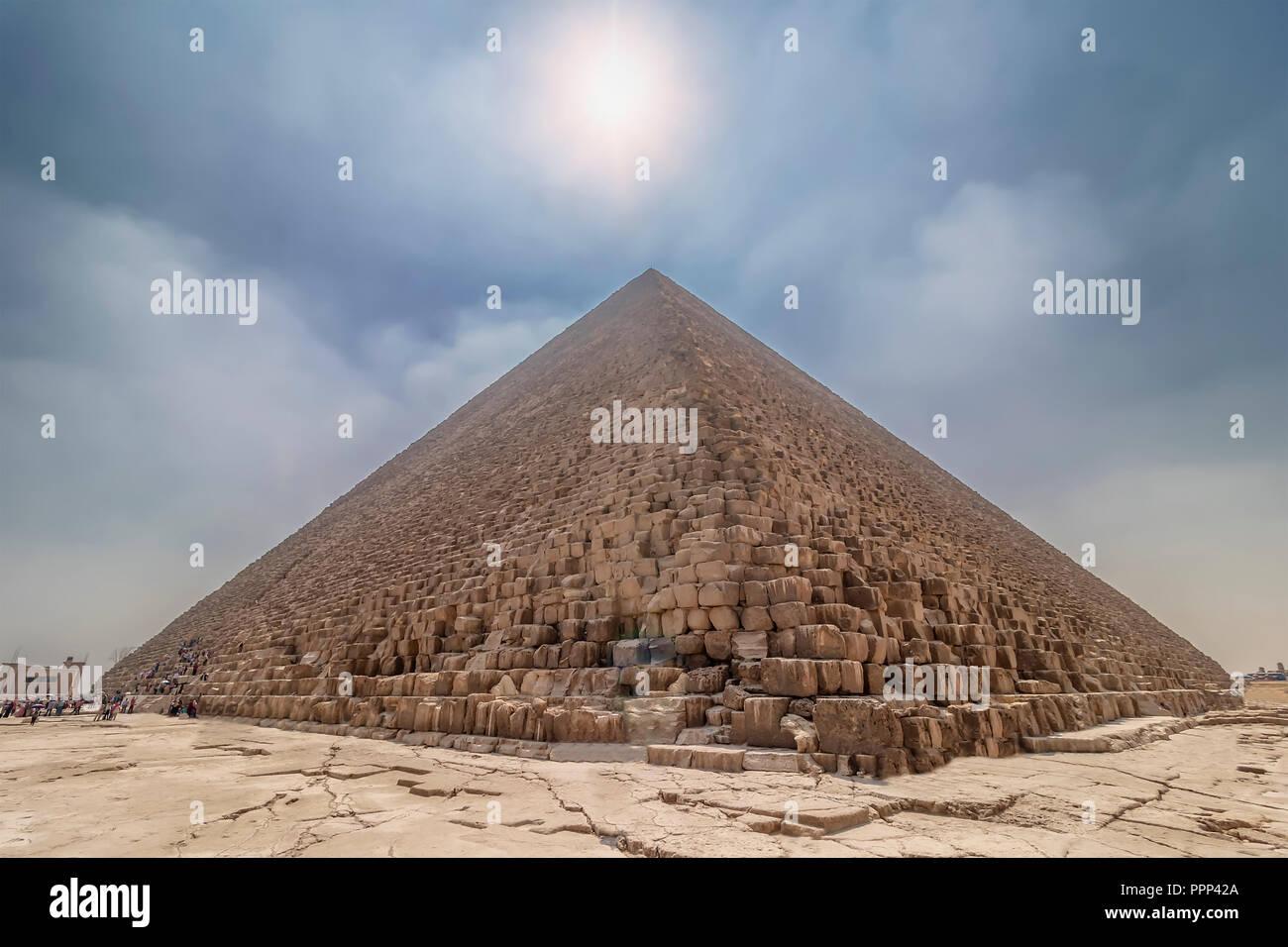 La Piramide di Cheope illuminata dal sole di retroilluminazione, con persone che entrano all'interno per visitare. La zona con le grandi piramidi di Giza in Egitto Immagini Stock