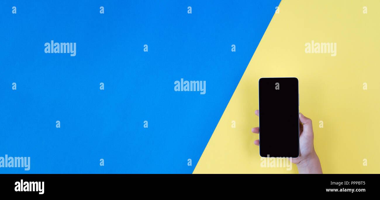 Mano Che Tiene Il Telefono Su Blu E Sfondo Giallo Foto Immagine