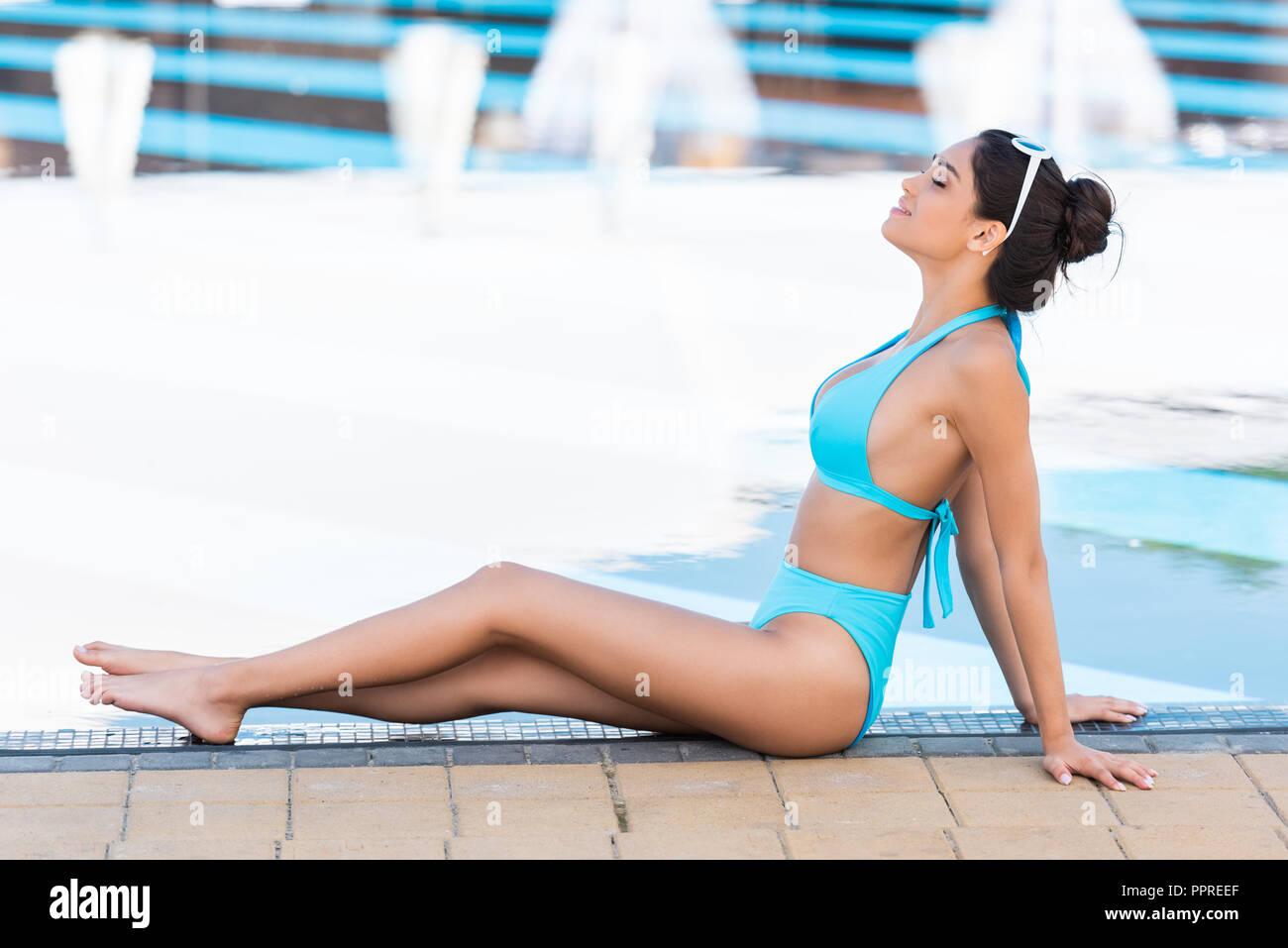 Ragazza abbronzata in bikini blu rilassarsi e prendere il sole a bordo piscina Immagini Stock
