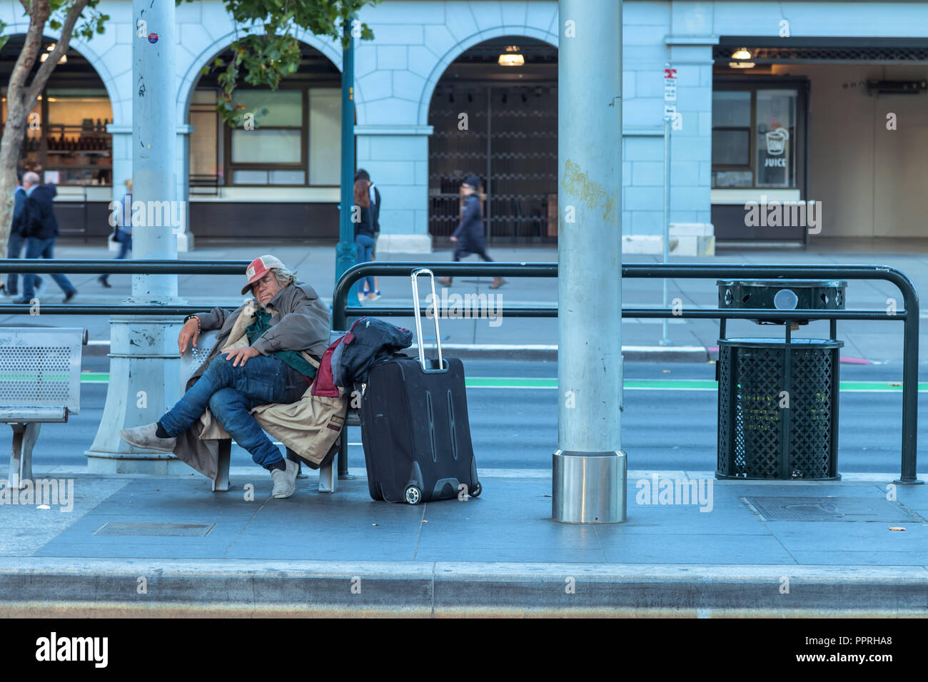 Un uomo senza tetto con i suoi beni dormiva su una panchina presso la stazione dei treni di San Francisco, California, Stati Uniti Immagini Stock