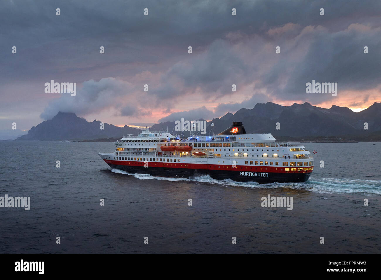 Il traghetto Hurtigruten, la signora FINNMARKEN, parte sud da Svolvær. Le suggestive montagne delle isole Lofoten e il sole di mezzanotte dietro la Norvegia. Foto Stock