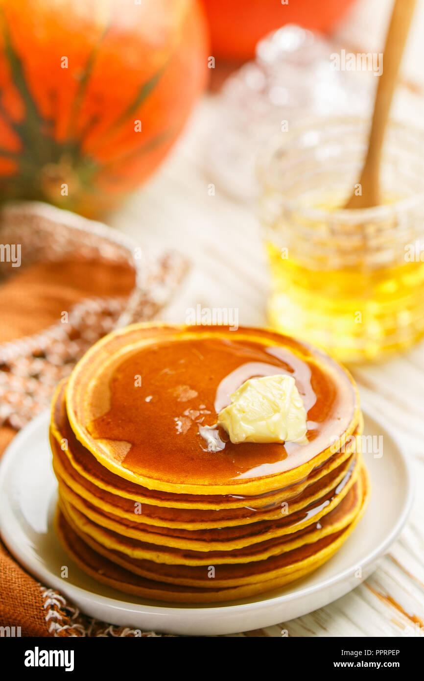 Freschi Fatti in casa frittella di zucca con il miele e il burro in una piastra bianca. Tradizionale gustoso sana colazione per buongustai. Messa a fuoco selettiva Immagini Stock