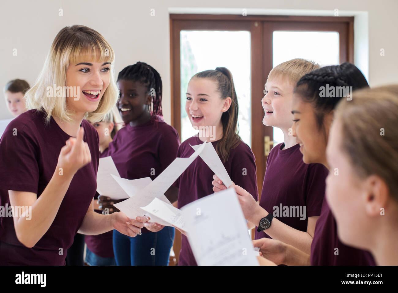 I bambini in coro scolastico essendo incoraggiati dall'insegnante Immagini Stock
