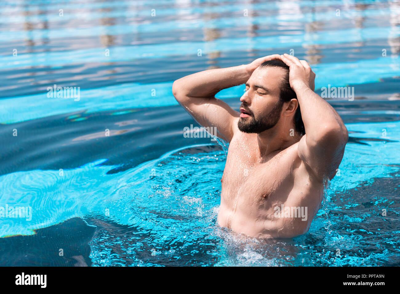 Uomo Barbuto con gli occhi chiusi in piedi in piscina Immagini Stock