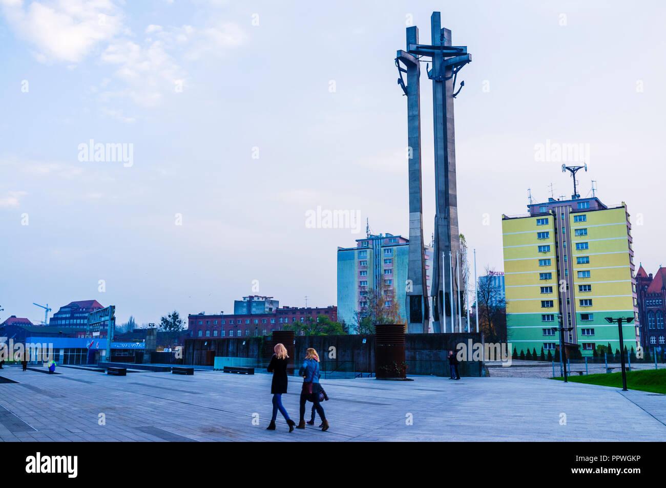 Gdansk, Pomerania, Polonia : due donne a piedi passato il Monumento ai Caduti i lavoratori del cantiere di 1970 alla solidarietà quadrato (Plac Solidarności) progettato Immagini Stock