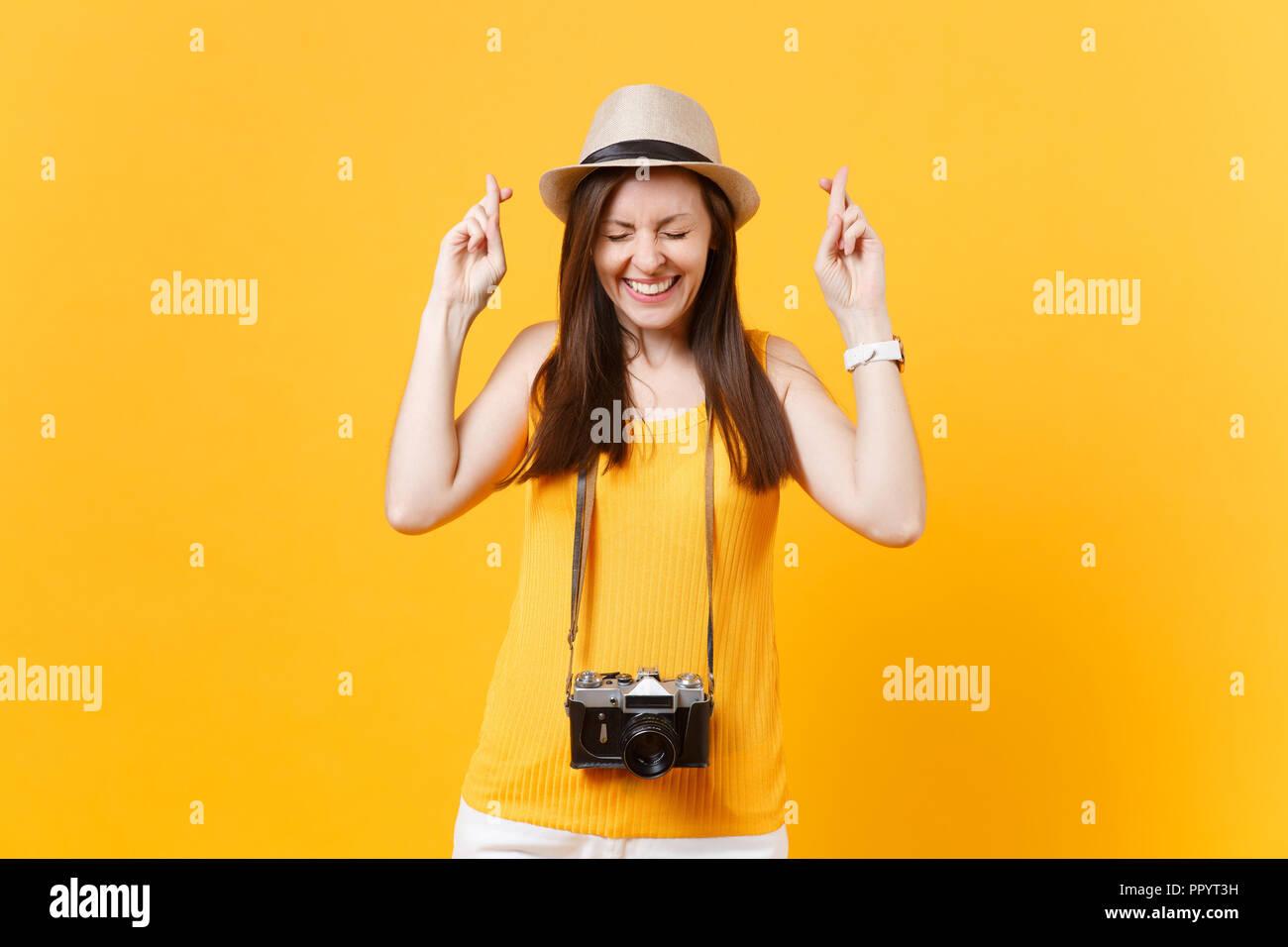 Donna turistica in estate abiti casual hat tenere le dita incrociate a occhi chiusi isolati su sfondo giallo. Femmina passeggero viaggia all'estero a trave Immagini Stock