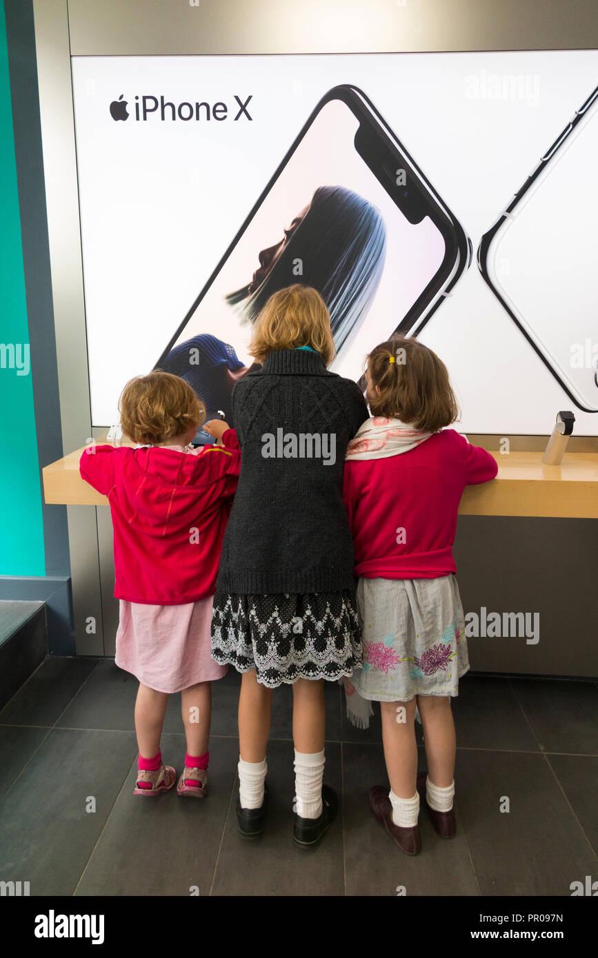 Le tre sorelle le ragazze / ragazza / bambino / bambino / bambini / bambino / bambini utilizzando un iPhone / i Phone X sul display e per la vendita in un negozio Apple shop. Regno Unito (102 Immagini Stock