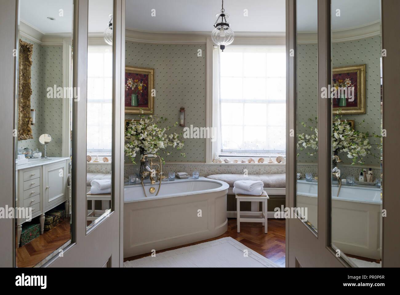 Vista attraverso le porte a specchio per bagno con carta da parati