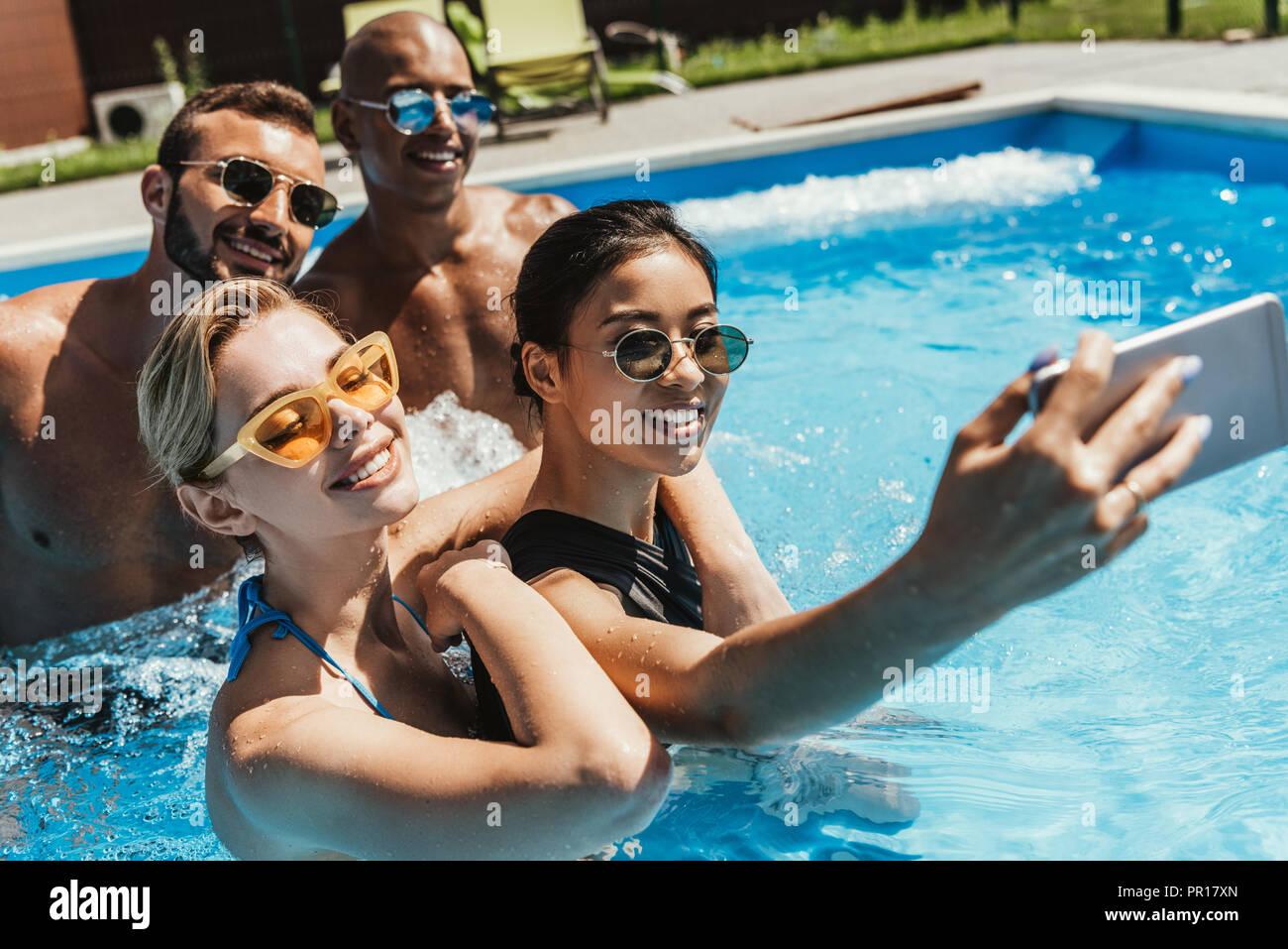 Coppie multiculturale in occhiali da sole prendendo selfie sullo smartphone in piscina Immagini Stock