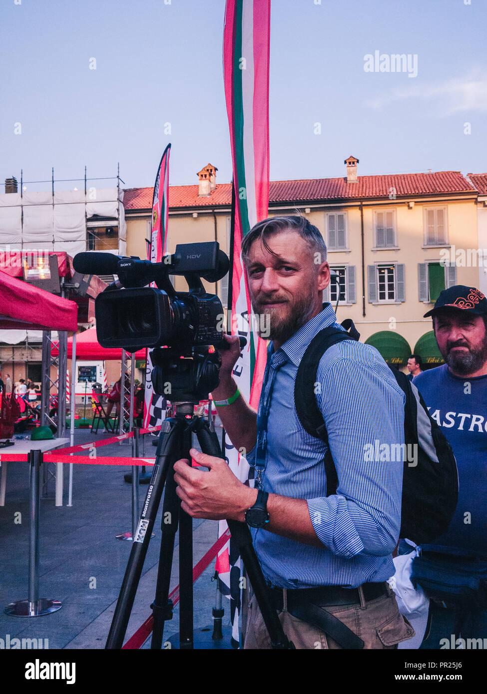 Snap di una telecamera uomo a Monza, Italia. Sembra sorpreso. Ci sono bandiere di tutti intorno a. Guarda sconvolto con un bel video della fotocamera e microfono treppiede Immagini Stock