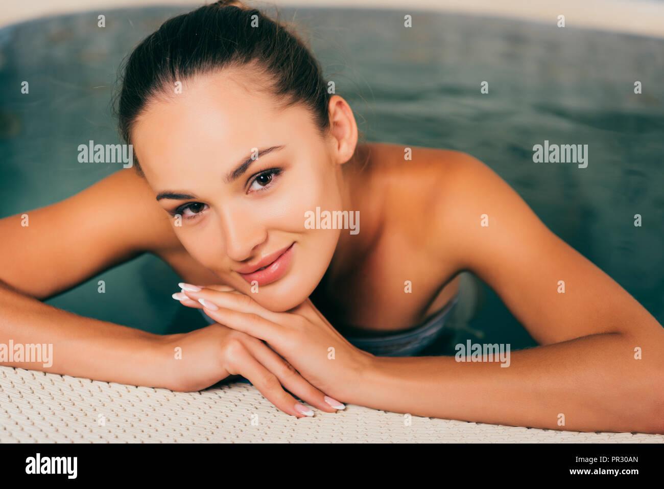 Donna rilassante in piscina e guardando la fotocamera Immagini Stock