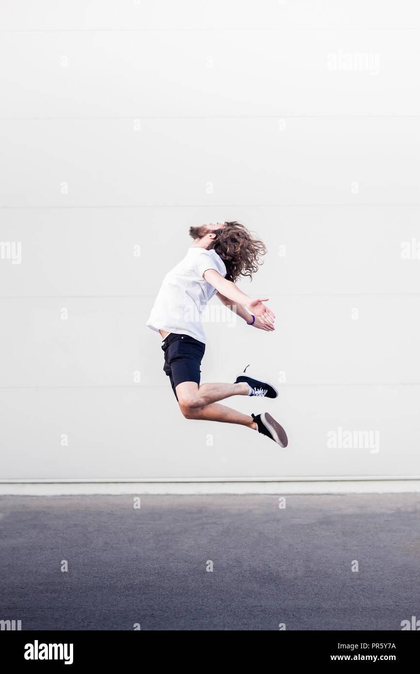 Giovane uomo in midair jump Immagini Stock