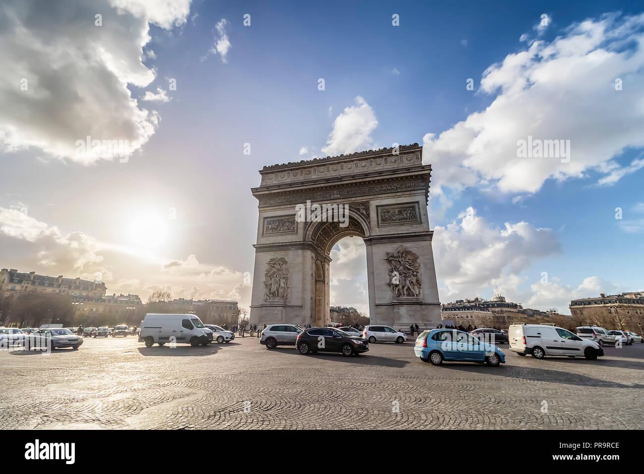 Arc de Triomphe con la trafficata strada di ciottoli, in controluce, al tramonto Immagini Stock