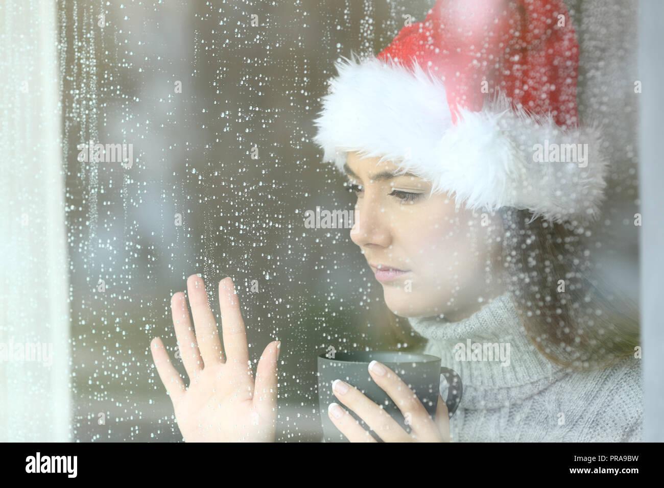 Triste e solitaria donna di guardare attraverso una finestra di vetro di  toccare con la mano 5c02eeb11031