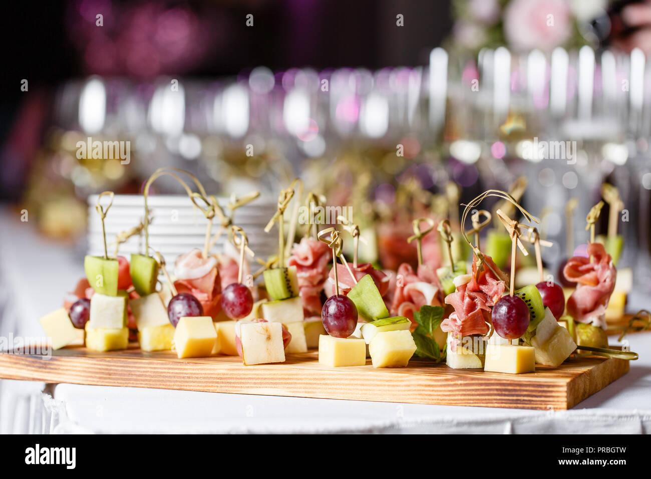 Il buffet presso la reception. Bicchieri di vino e champagne. Assortimento di tartine sulla tavola di legno. Servizio banchetti. catering food, snack al formaggio, prosciutto, prosciutto e frutta Immagini Stock