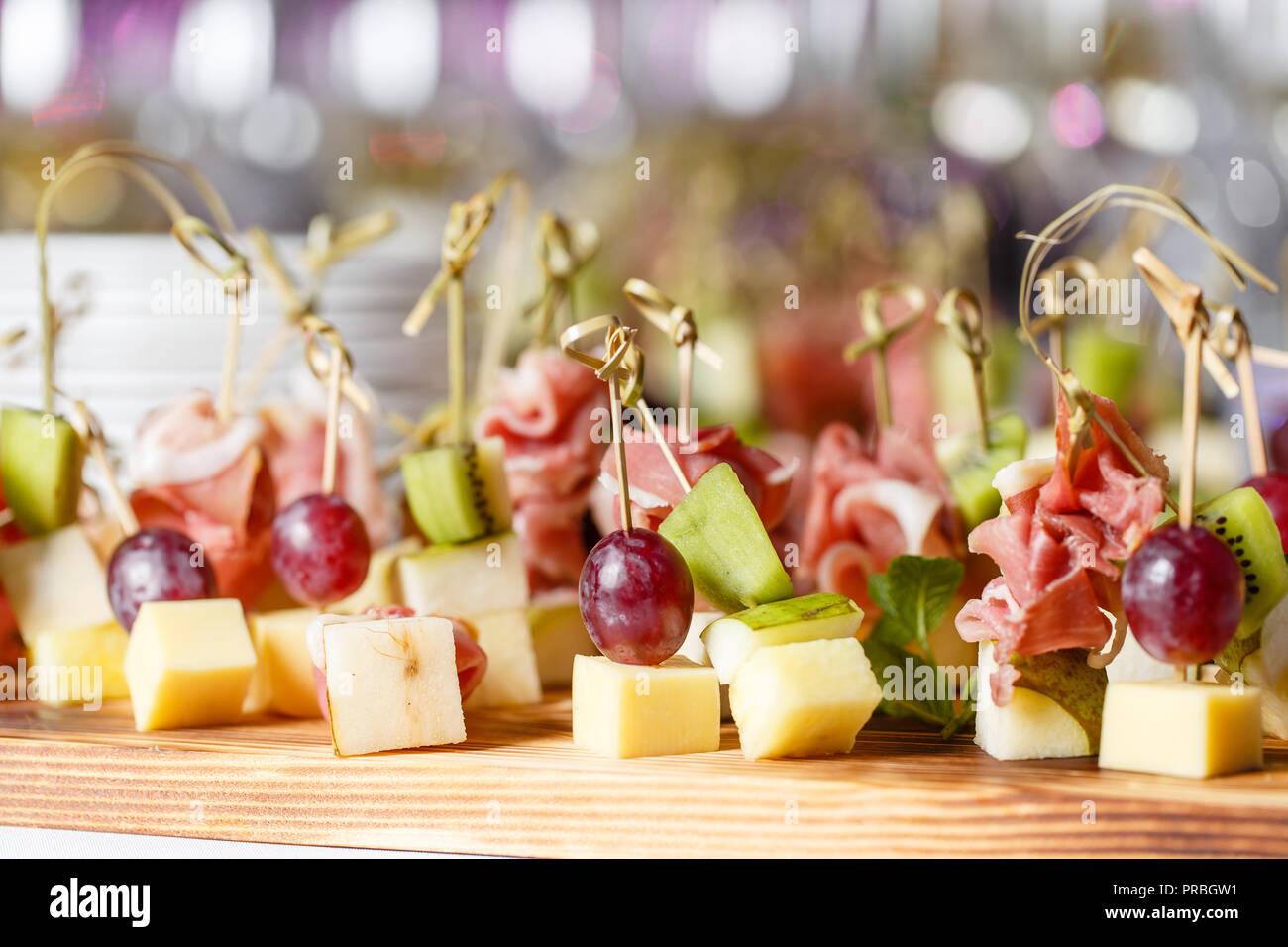 Il buffet presso la reception. Assortimento di tartine sulla tavola di legno. Servizio banchetti. catering food, snack al formaggio, prosciutto, prosciutto e frutta Immagini Stock