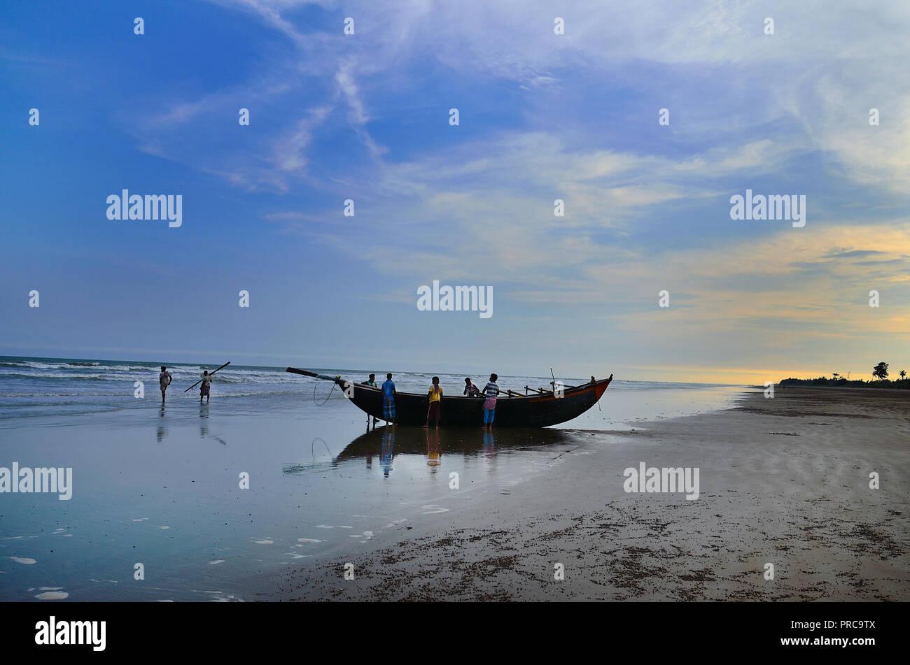 I pescatori con la loro barca al tramonto, Lal Kankra beach in teh Midnapore distretto di West Bengal, India.Il suo un telecomando e tranquillo villaggio di pescatori. Immagini Stock