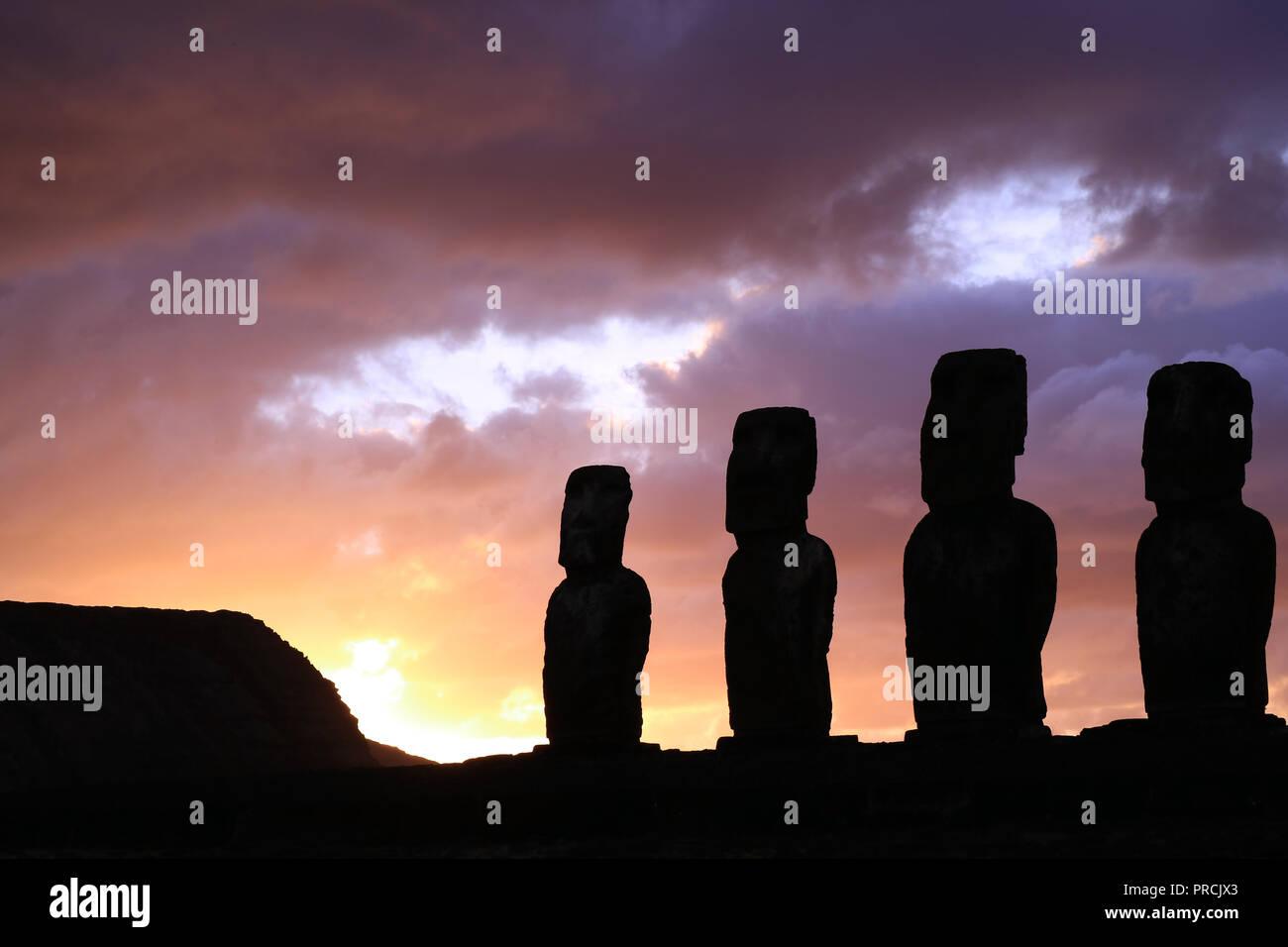 Stordimento viola Sunrise cielo nuvoloso oltre la sagoma del gigante Moai statue di Ahu Tongariki sito archeologico, Isola di Pasqua, Cile Immagini Stock
