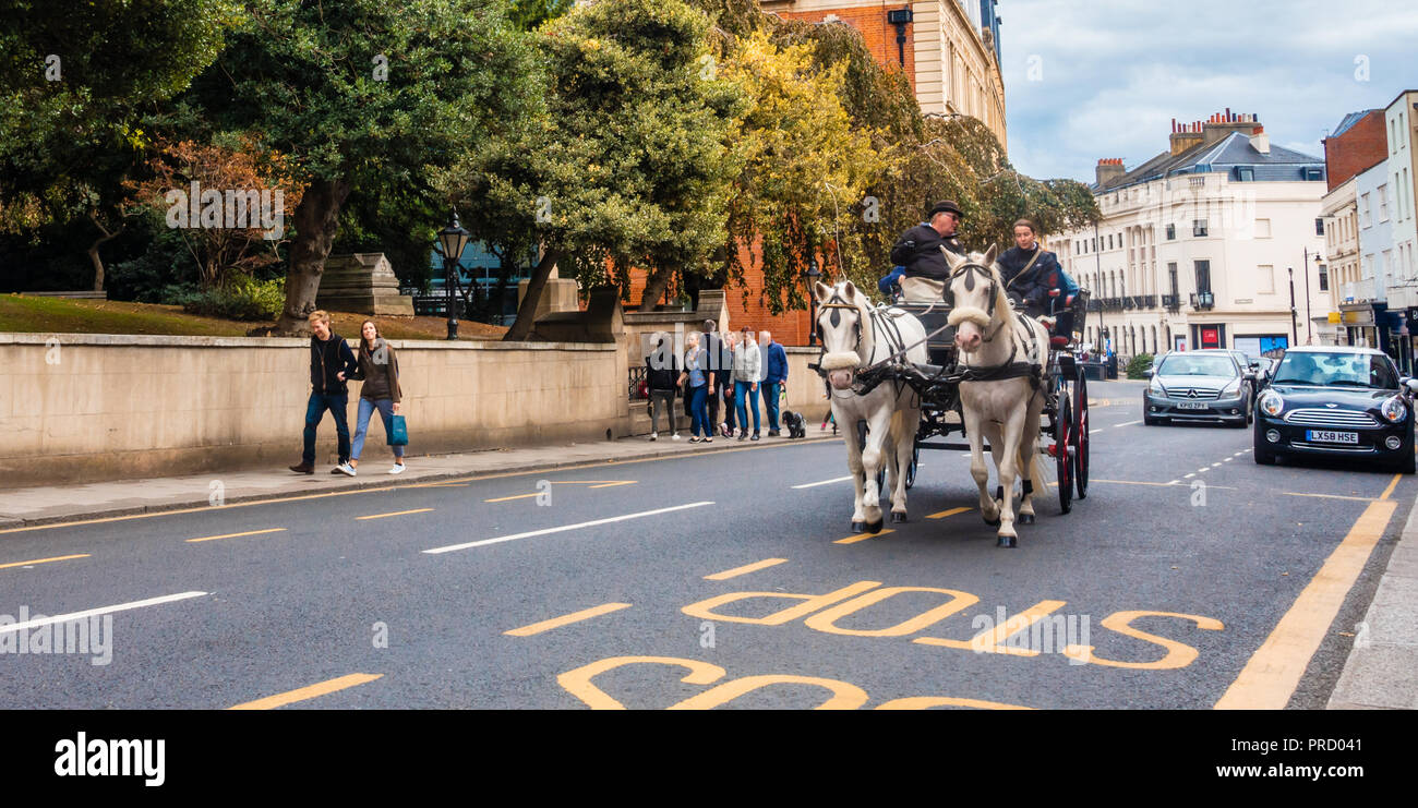 Un carro trainato da cavalli trot giù il High Street in Windsor, Regno Unito. Immagini Stock
