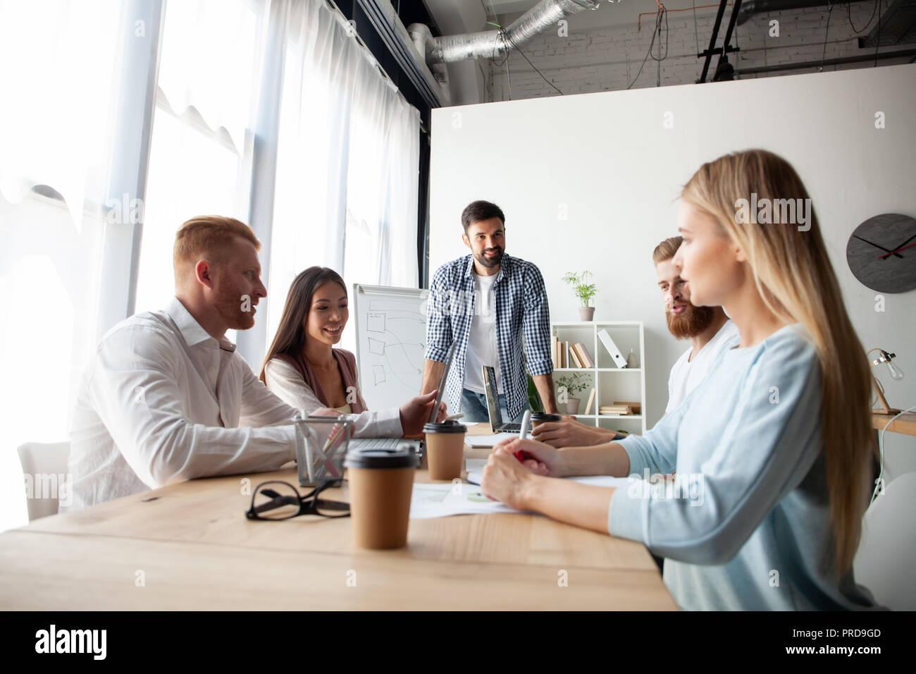 Giovane team di collaboratori di grande discussione aziendale nel moderno ufficio coworking.Il lavoro di squadra di persone concetto Immagini Stock