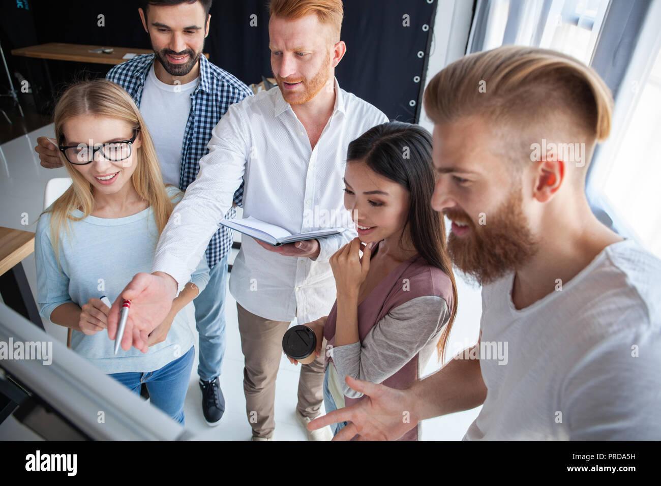Gruppo di colleghi giovani vestiti casual in piedi insieme in un ufficio moderno e di brainstorming. Immagini Stock