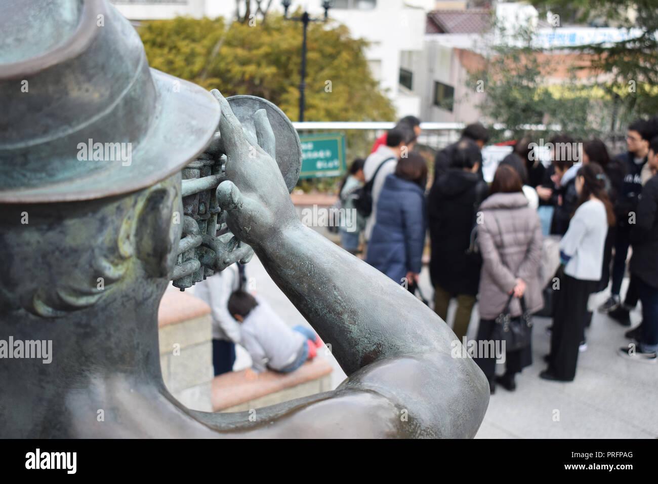 Raduno di persone con statua in primo piano nel Kitanocho, Kobe, Giappone Immagini Stock