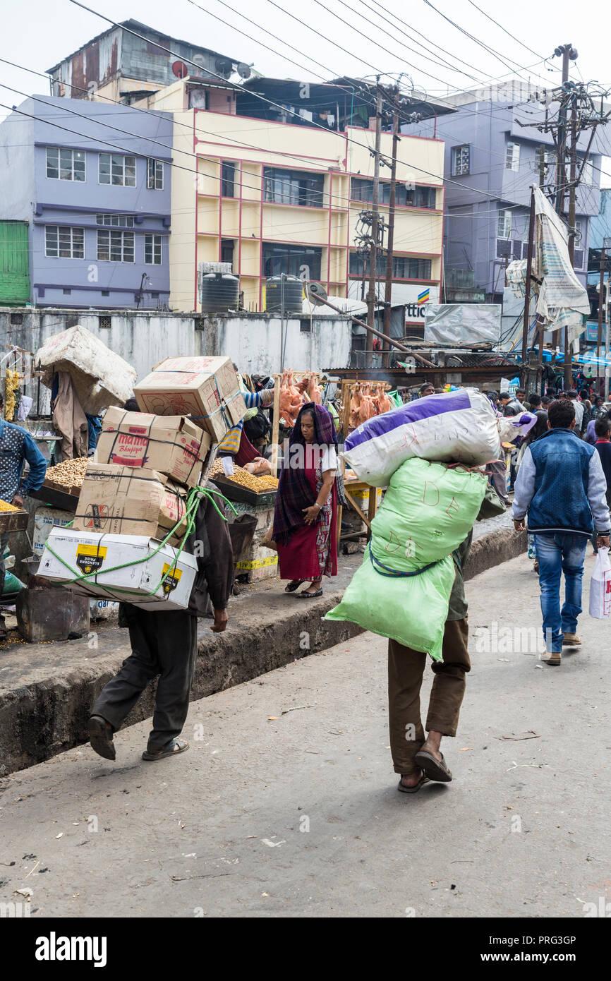 Gli uomini che trasportano carichi pesanti sulle loro spalle, Shillong, Meghalaya, India Immagini Stock