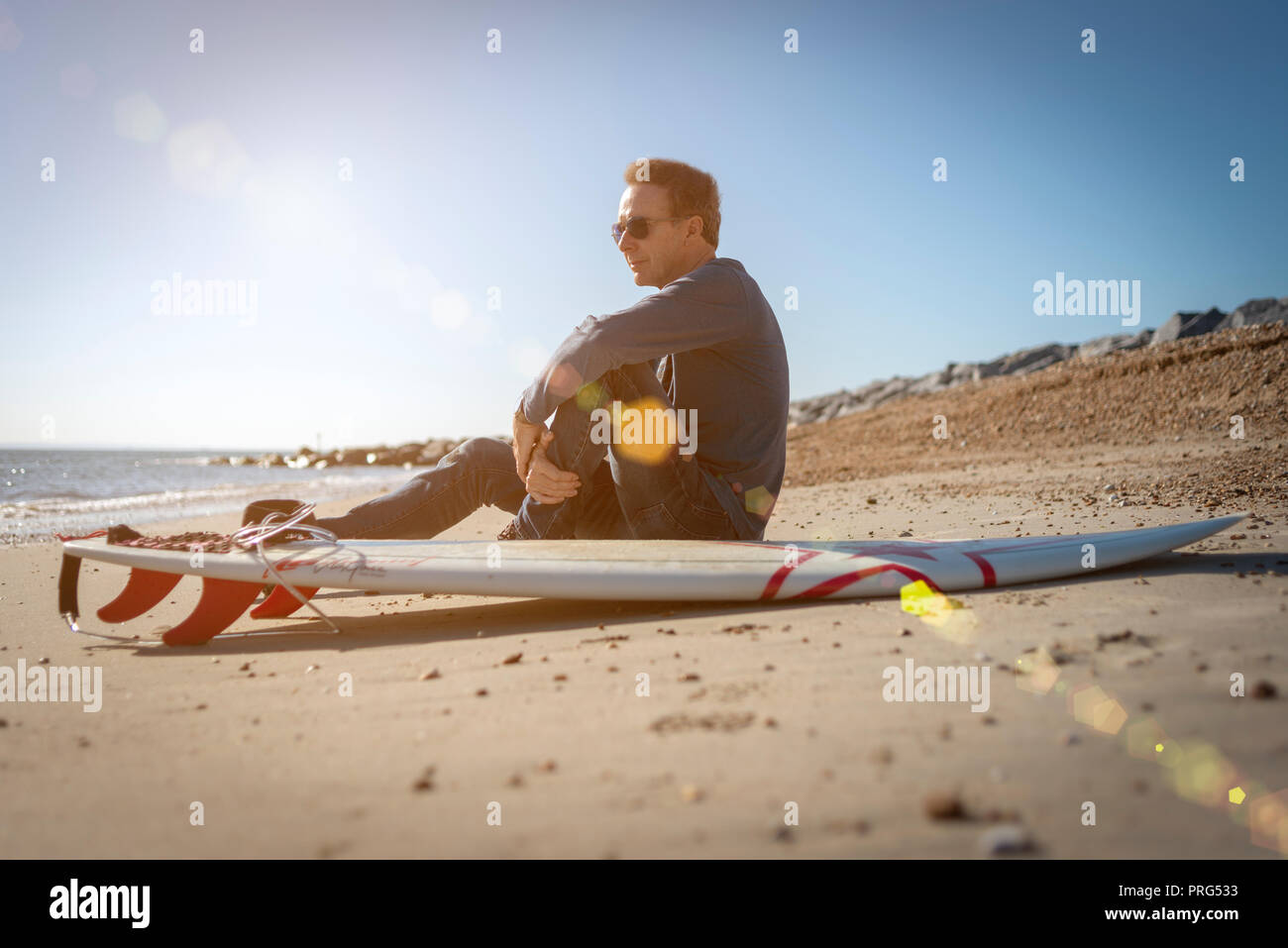Maschio maturo surfer seduto sulla spiaggia con una tavola da surf a guardare le onde, lens flare Foto Stock