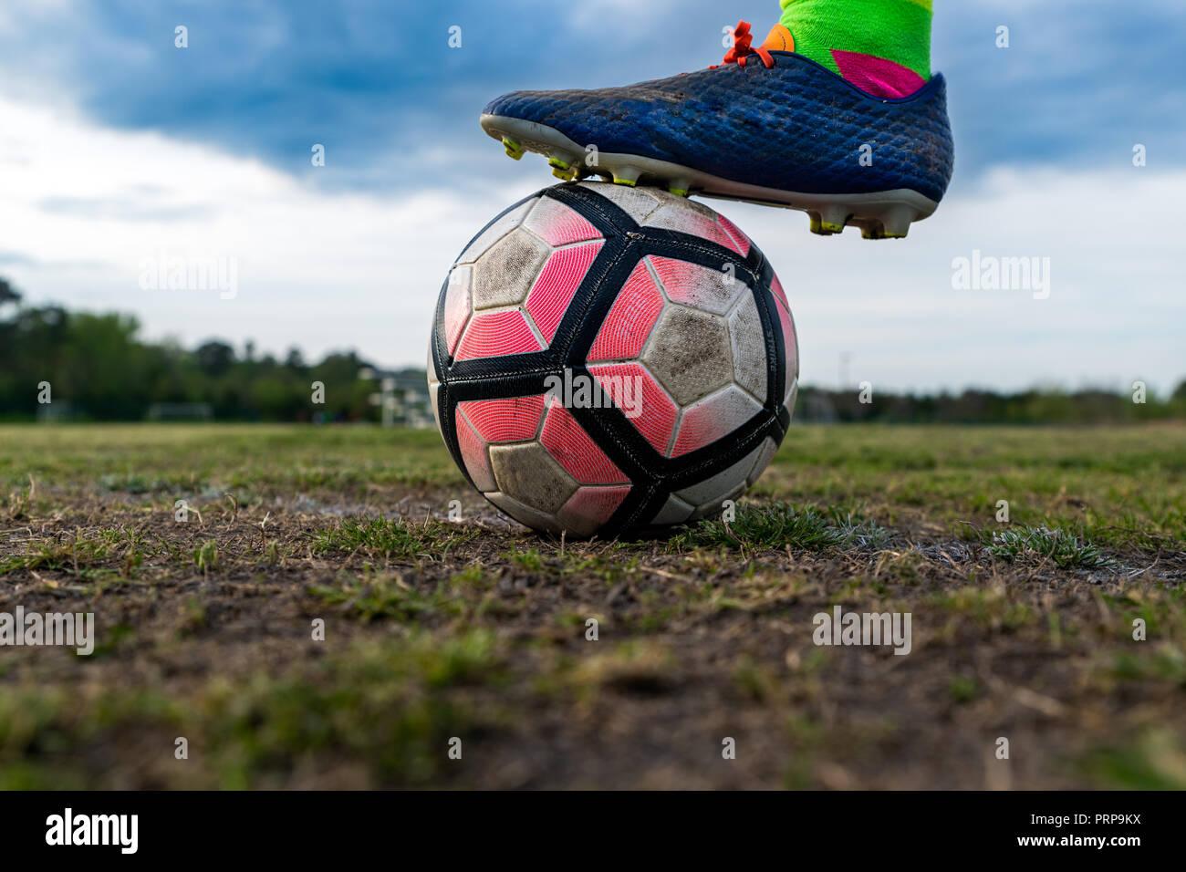 Un giovane atleta mette loro cibo cleated su un pallone da calcio. Concetti: sport giovanile, atleta, focus, preparazione pratica, intensità, aspirazione, sogno Immagini Stock