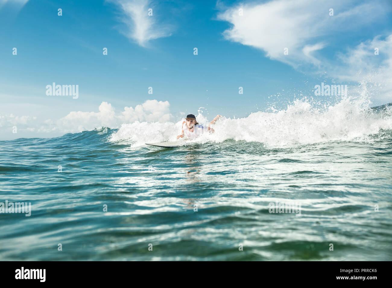 Surfista maschio nuotare sulla scheda di navigazione in oceano presso la spiaggia di Nusa Dua, Bali, Indonesia Immagini Stock