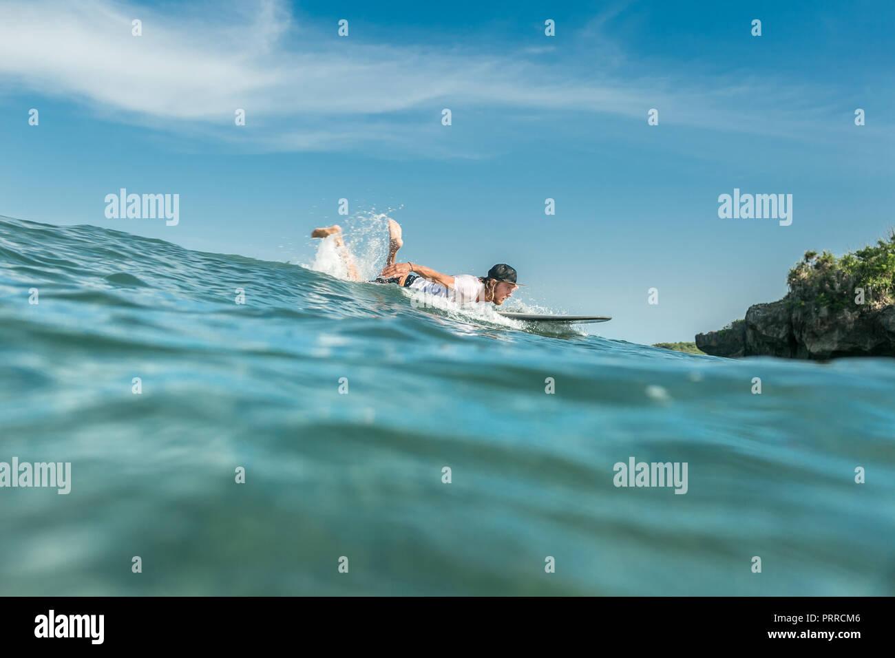 Giovane atleta maschio nuotare sulla scheda di navigazione in oceano presso la spiaggia di Nusa Dua, Bali, Indonesia Immagini Stock