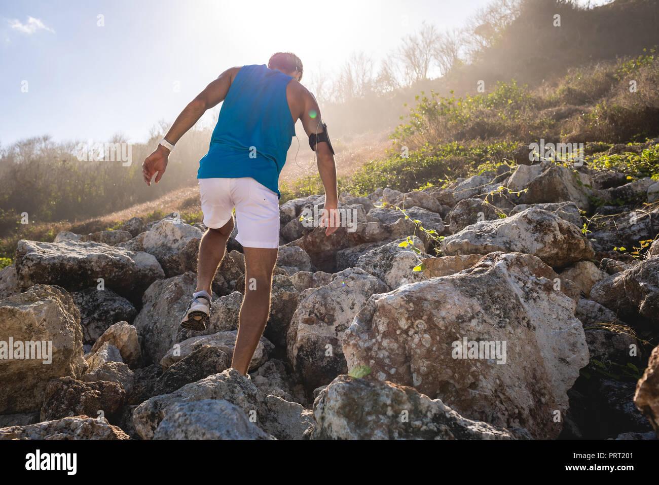 Vista posteriore del uomo atletico arrampicata sulle rocce della montagna con retro illuminazione Immagini Stock
