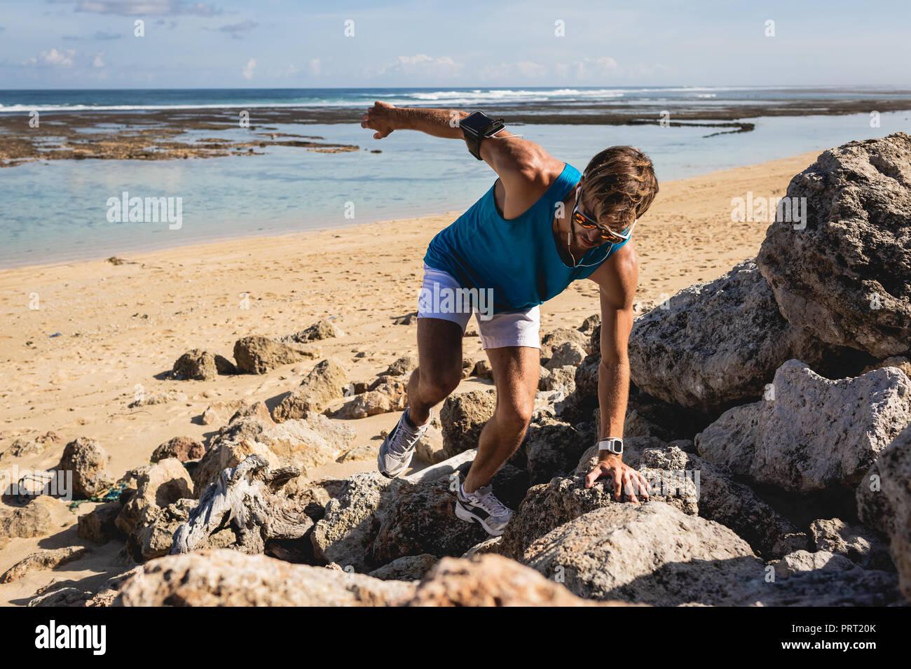 Sportivo arrampicata sulle rocce sulla spiaggia, Bali, Indonesia Immagini Stock