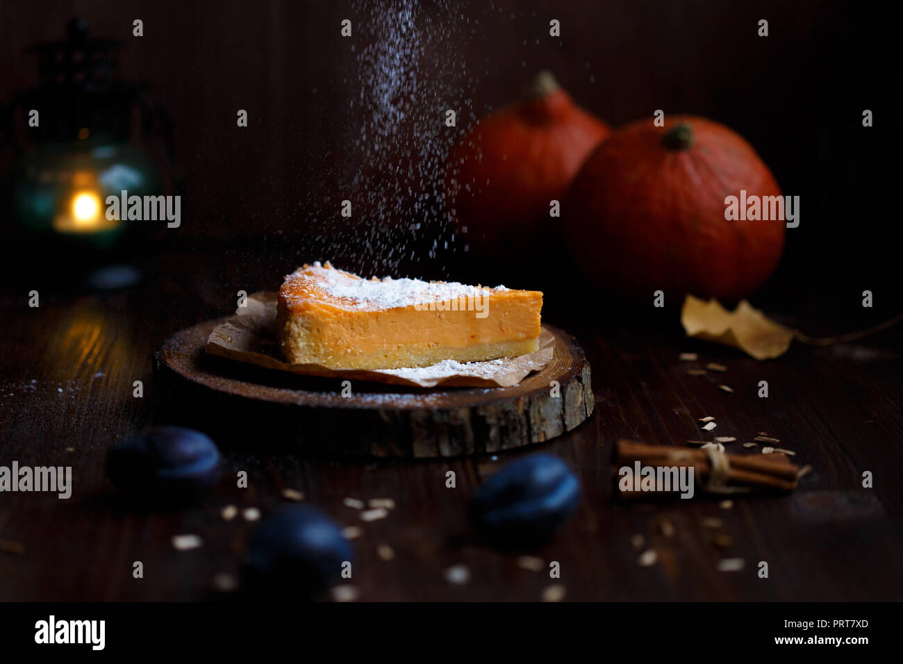 Femmina lato un pizzico di zucchero in polvere sul Cheesecake alla zucca. Zucche, lampada da tavolo, fogliame, vaniglia su un di legno scuro dello sfondo. In autunno e in inverno, concetto accogliente Immagini Stock